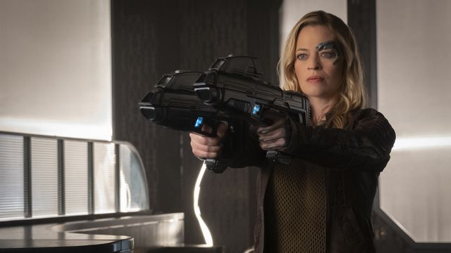A determined-looking blonde woman with Borg face implants —Seven of Nine from Star Trek: Voyager, played by Jeri Ryan — points two phaser rifles at a target offscreen.