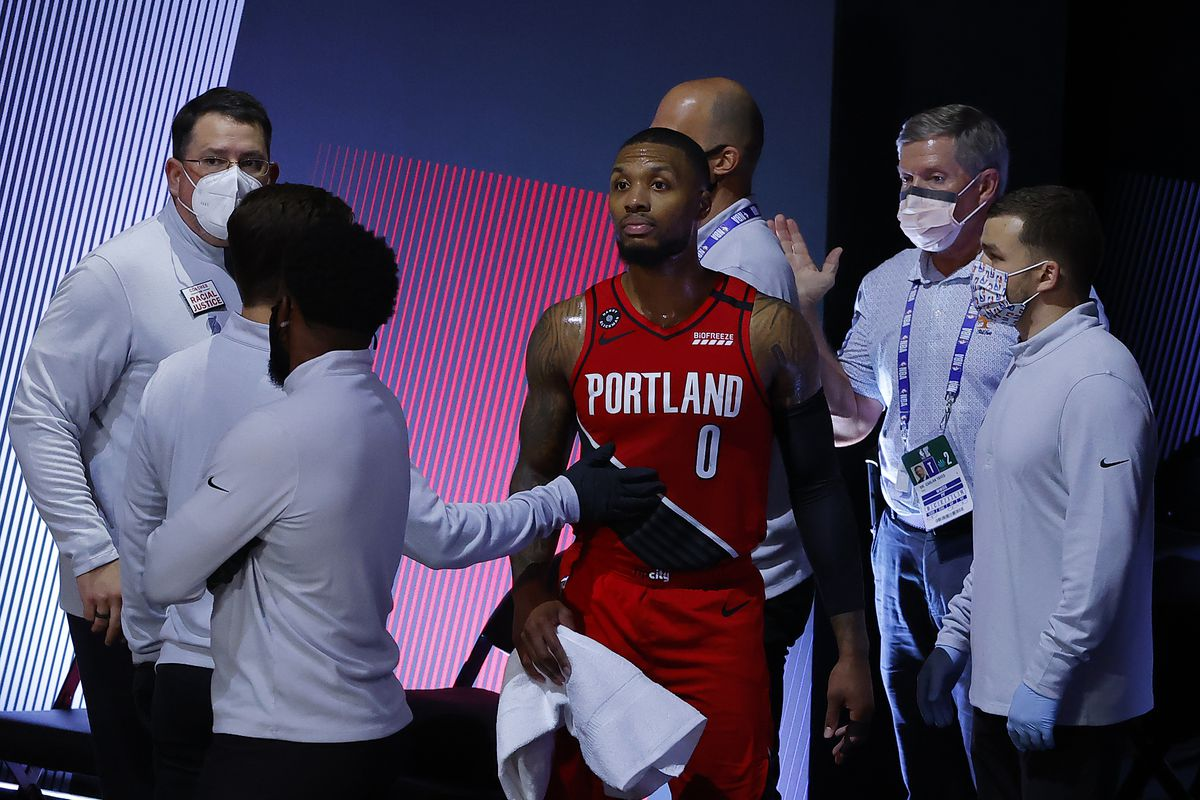 Damian Lillard of the Portland Trail Blazers is tended to after hurting his finger during the third quarter against the Los Angeles Lakers in Game Two of the Western Conference First Round during the 2020 NBA Playoffs at AdventHealth Arena at ESPN Wide World Of Sports Complex on August 20, 2020 in Lake Buena Vista, Florida.
