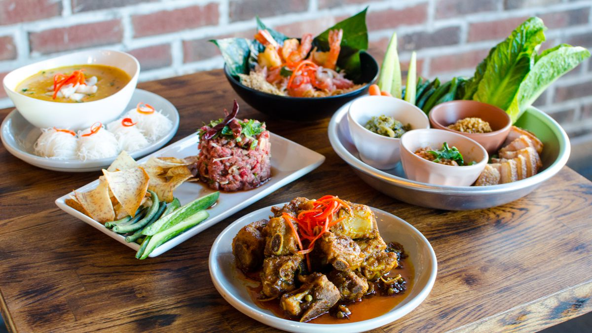 Five Thai dishes sit on a wooden table in front of a brick wall. There's a curry, a pomelo salad with shrimp, a large pile of pork ribs, and more.