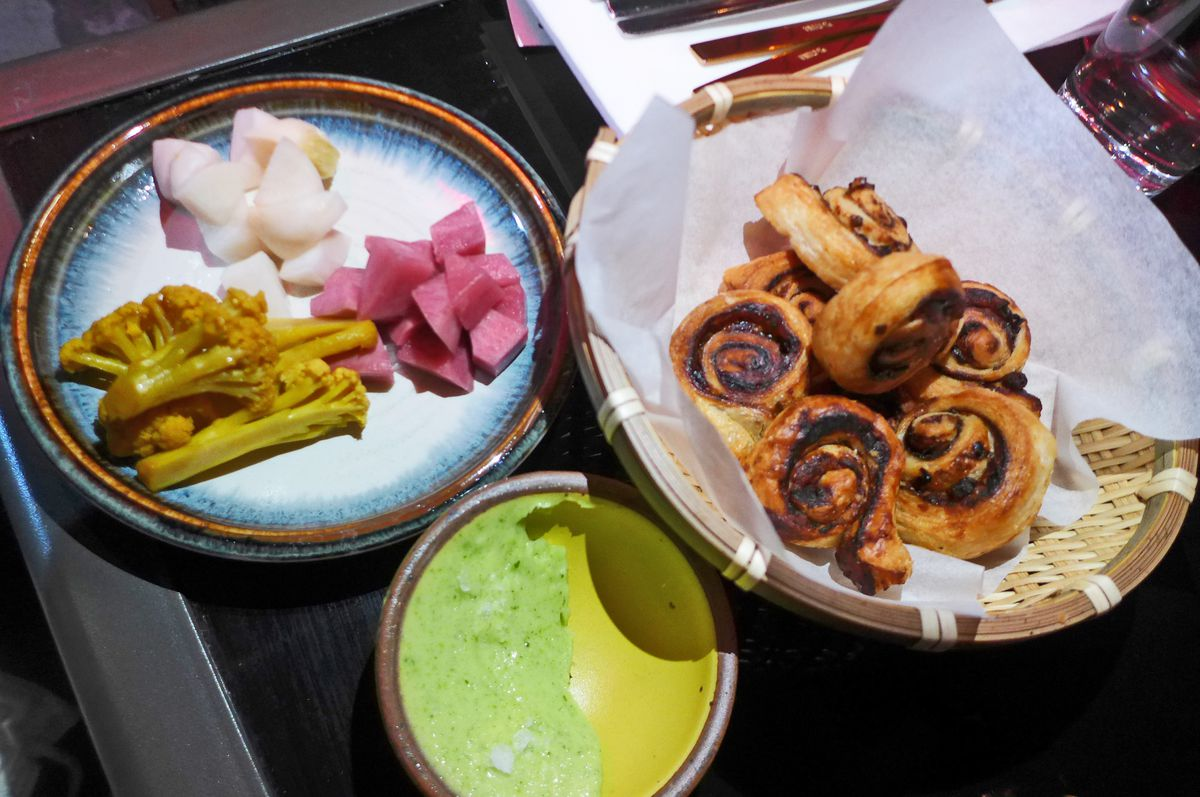 Three elements include a basket of browned small rolls, green butter smeared across a yellow saucer, and a plate of pickles,