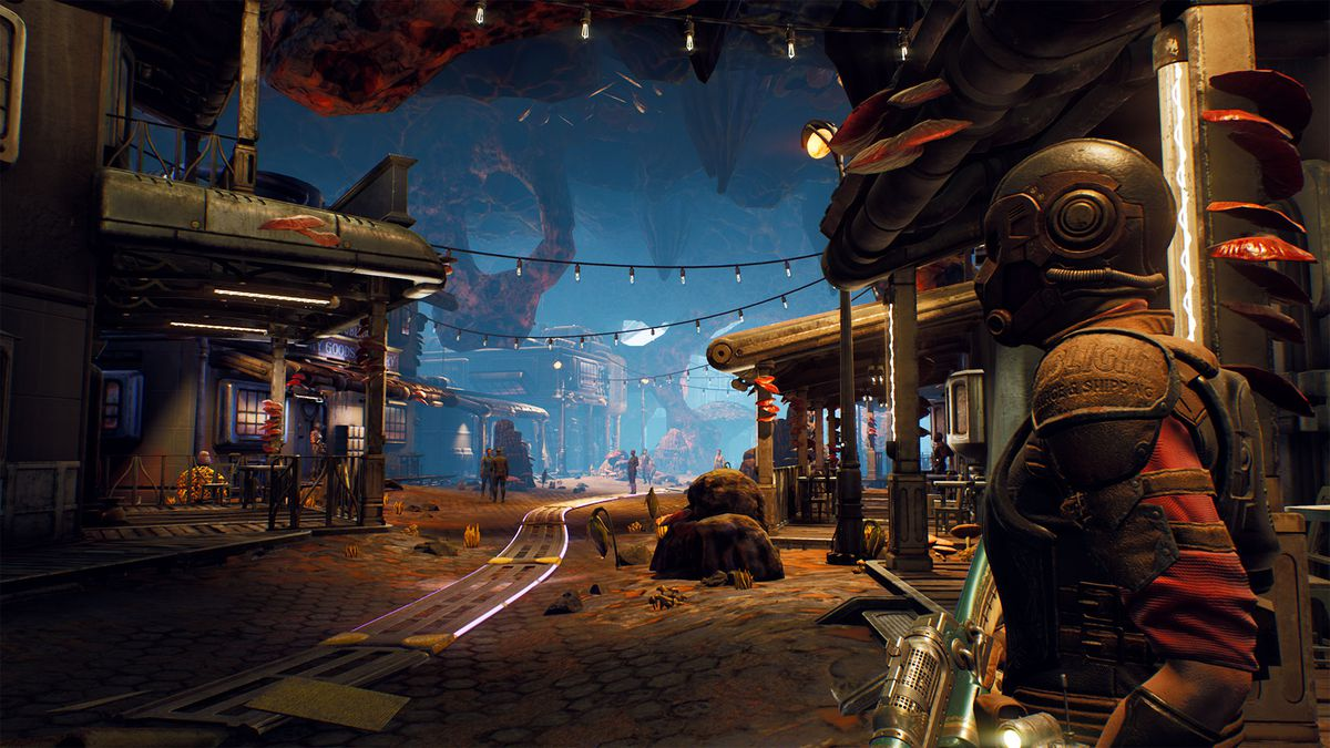 a scene from Fallbrook, a zone in The Outer Worlds, with a figure in a spacesuit standing on a main street in a cave environment