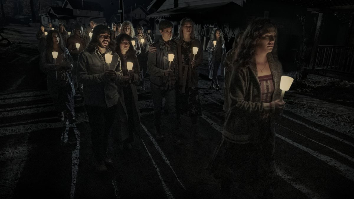 a congregation of people walking in the dark while holding candles