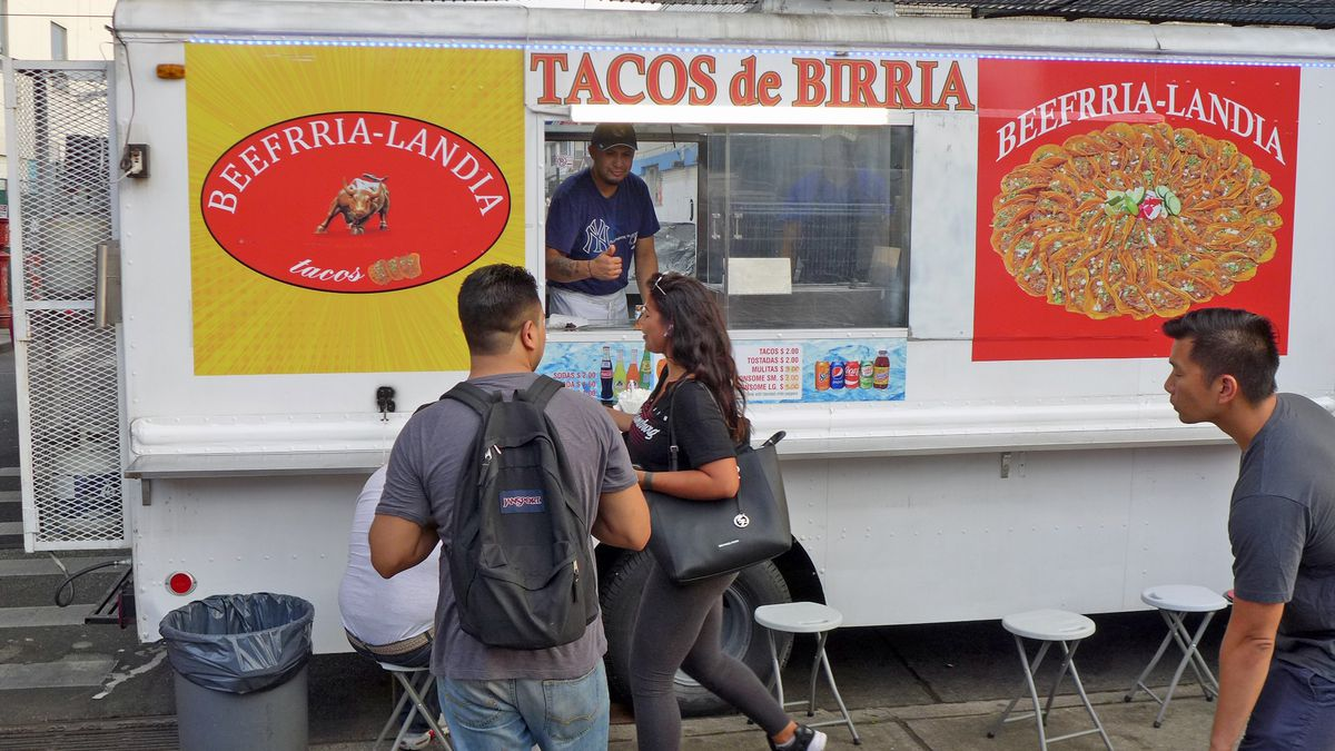 A white panels truck with a man leaning out the window and pictures of birria tacos on the side...