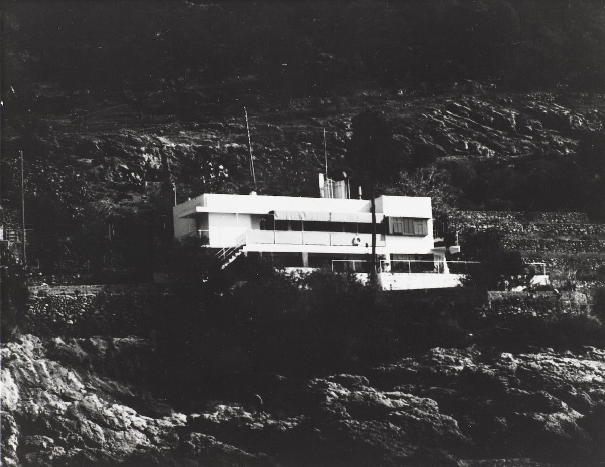 A black and white photo showing a rectilinear white house in a hill.