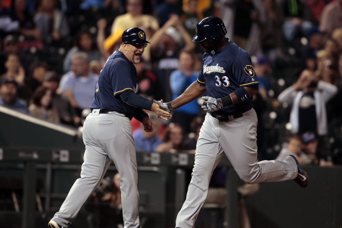 Chris Carter slaps hands with his third base coach while rounding the bases after hitting a home run for the Brewers.