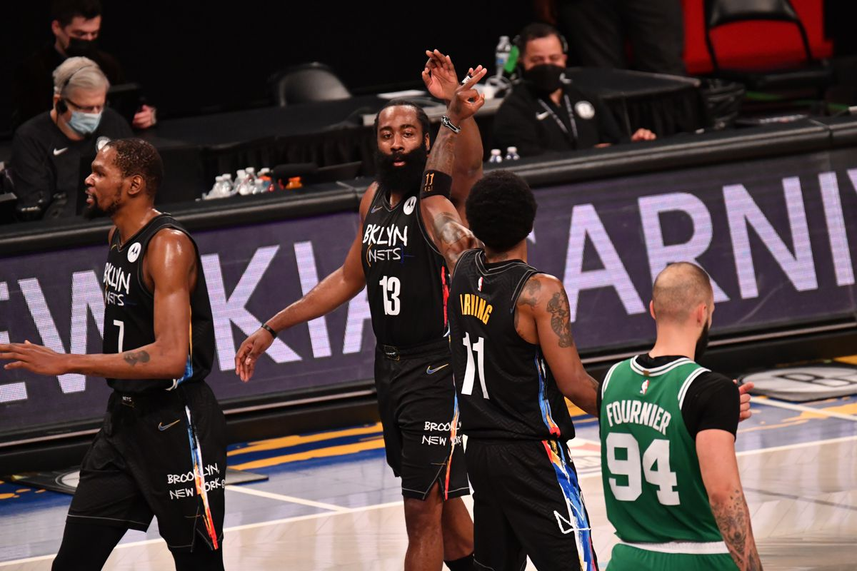 James Harden of the Brooklyn Nets and Kyrie Irving of the Brooklyn Nets high-five during a game against the Boston Celtics during Round One Game Two on May 25, 2021 at Barclays Center in Brooklyn, New York.