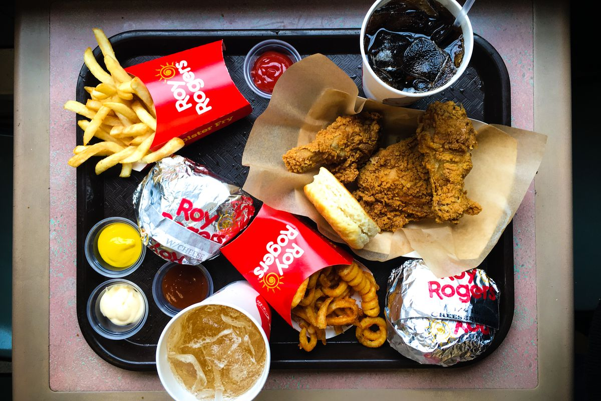 A tray of burgers, fried chicken, sauces, and drinks from Roy Rogers