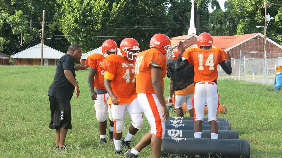 Northside's new football coach gets players started on a drill.