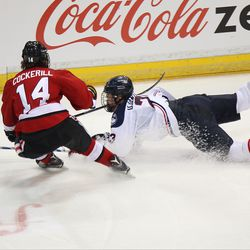 UConn's Kasperi Ojantakanen (23) dives to try and clear the puck in front of Northeastern's Garrett Cockerill (14).