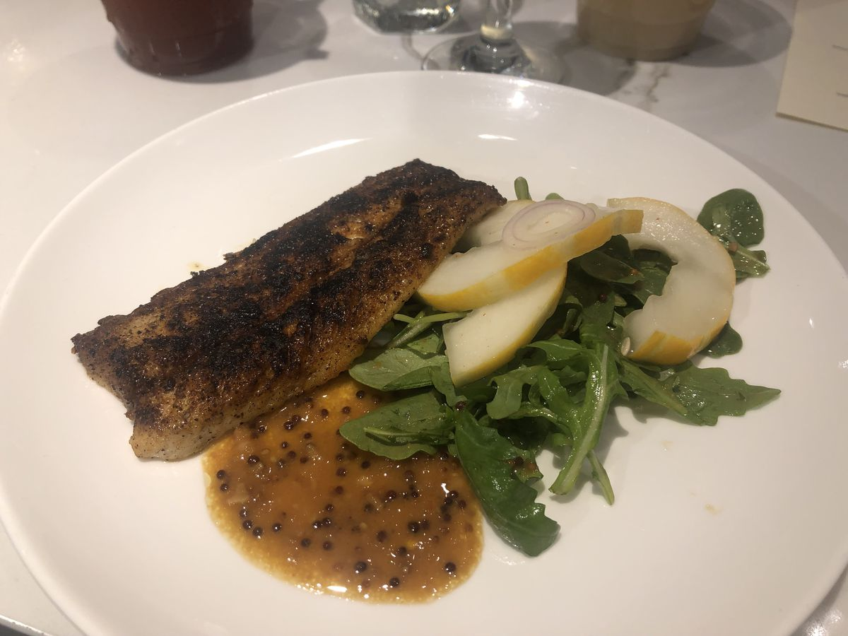 A white dish with a brown fish fillet laid next to an orange sauce, green leaves of arugula, and yellow-skinned slices of melon