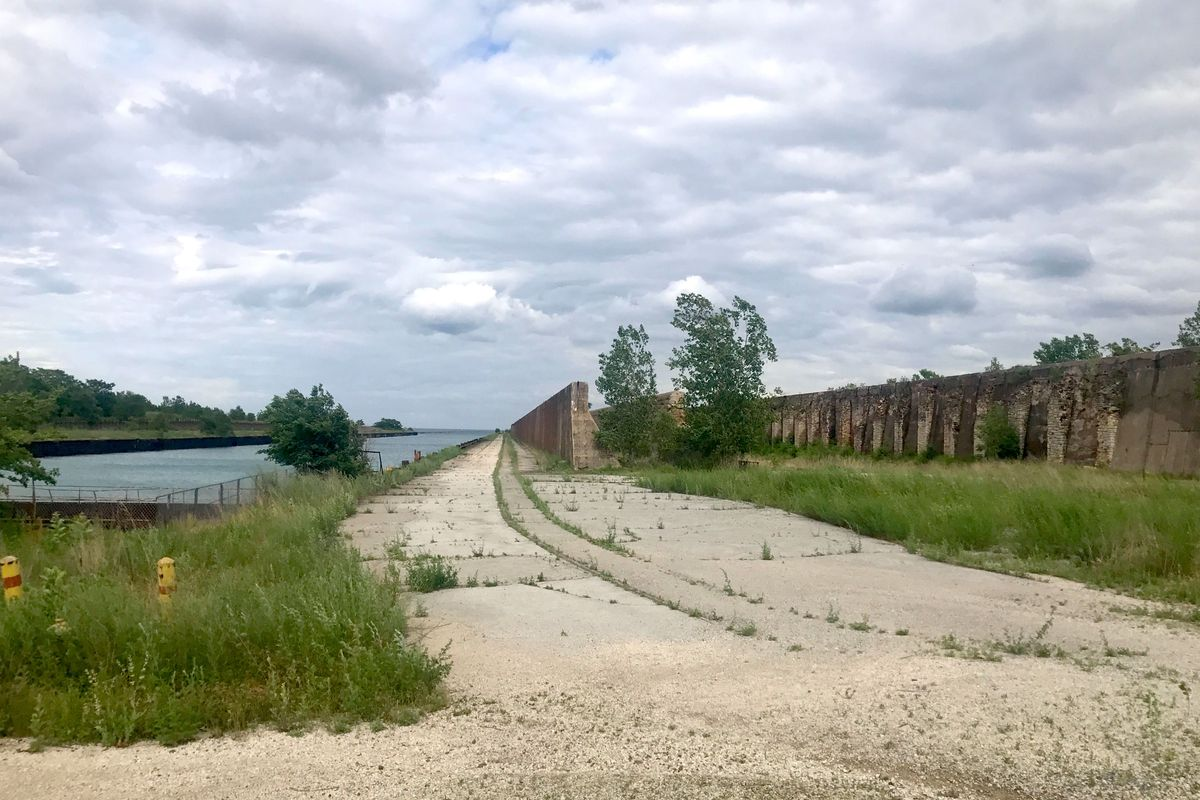 A vacant, weed-covered site with a long concrete wall and canal beneath a cloudy sky.