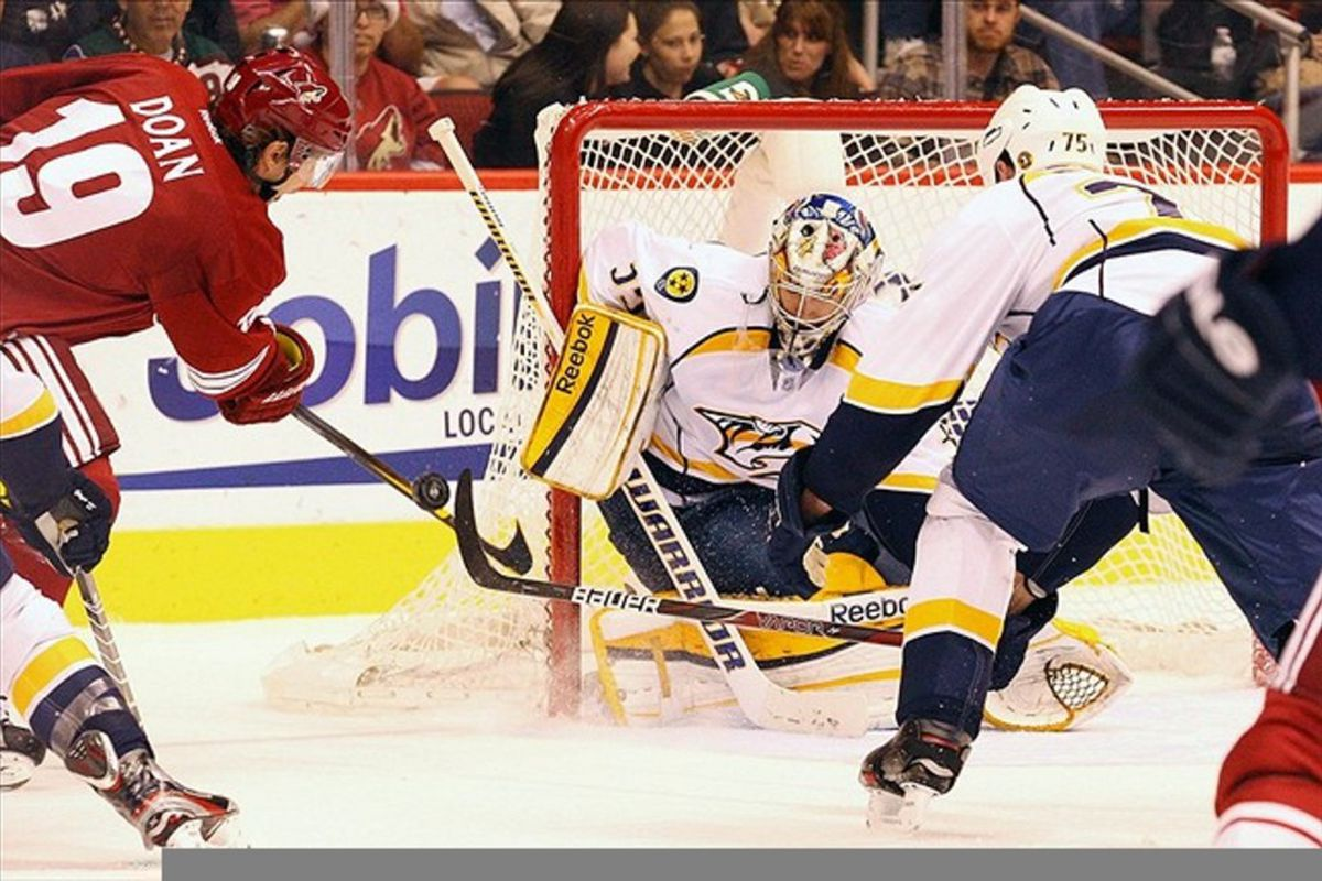 Mar 12, 2012; Glendale, AZ, USA; Nashville Predators goalie Pekka Rinne (center) defends the net against a shot by Phoenix Coyotes right wing Shane Doan (19) during the second period at Jobing.com Arena.  Mandatory Credit: Jake Roth-US PRESSWIRE