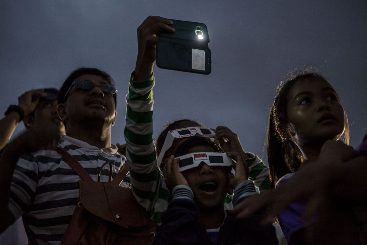 People gather during a total solar eclipse in 2016 in Palembang, South Sumatra province, Indonesia.