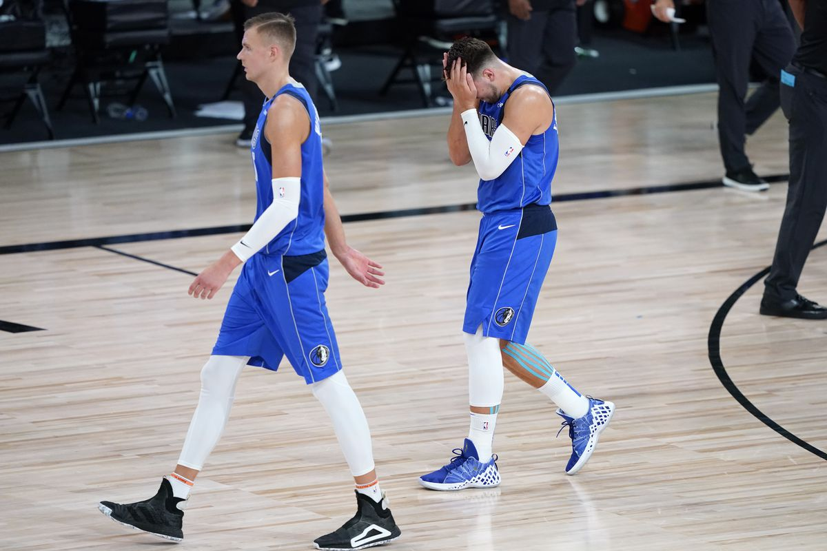 Dallas Mavericks players Kristaps Porzingis, left, and Luka Doncic leave the court after the first half of an NBA basketball first round playoff game against the Los Angeles Clippersat AdventHealth Arena.