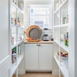 What was an attached outhouse some 130 years ago is now a convenient and practical storage pantry, hidden behind tall cabinet doors.