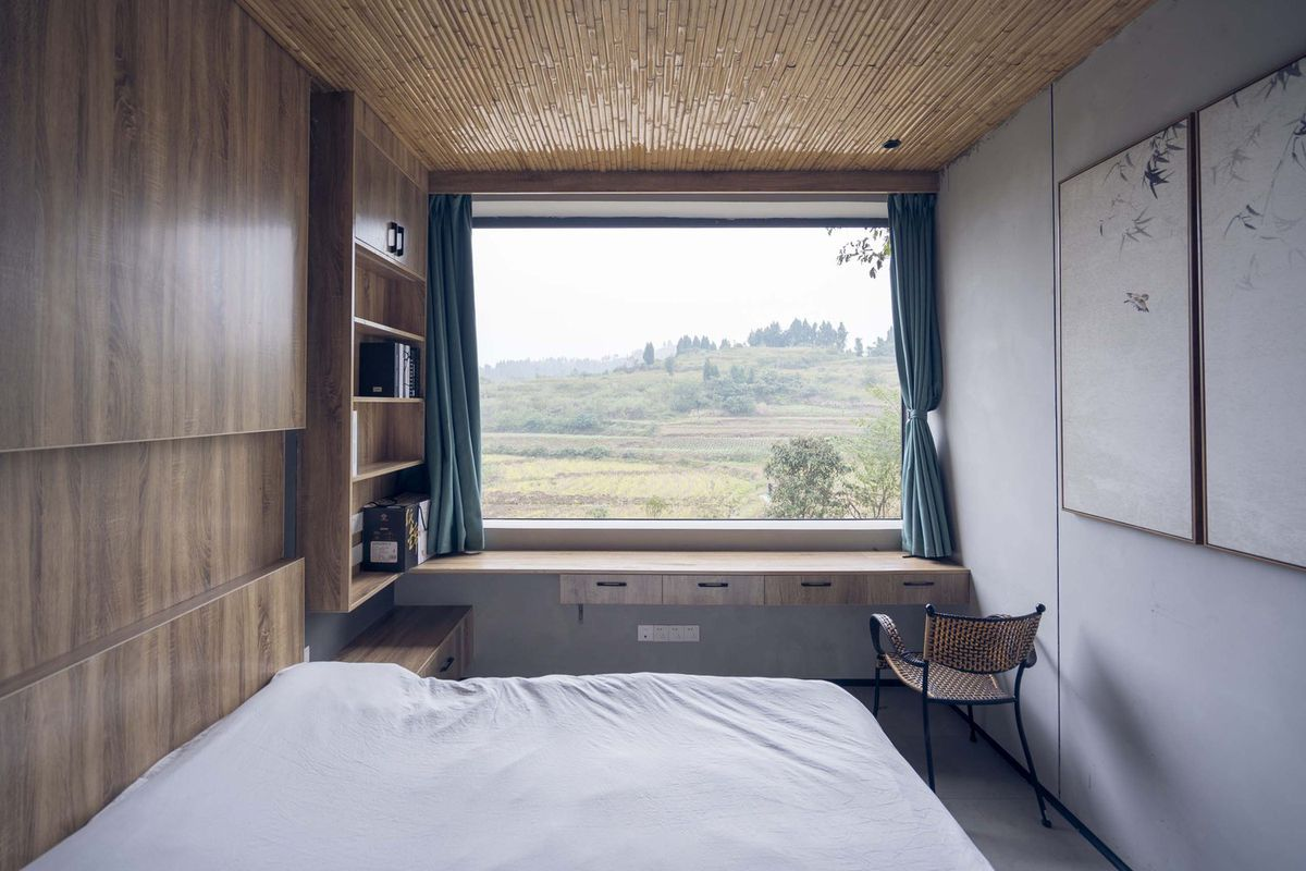 Bedroom with window looking out onto landscape.