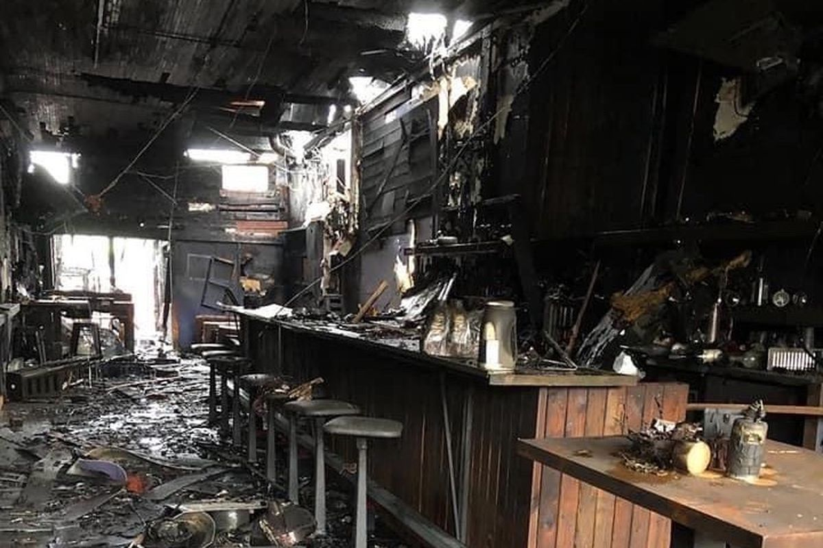 The fire-damaged interior to the Lumber Yard Bar in White Center, with rubble strewn on the floor and blackened walls