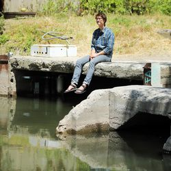 """Brian Tonetti, of the Seven Canyons Trust, talks about a proposal to """"daylight"""" the confluence of three Salt Lake Valley creeks — Emigration, Red Butte and Parleys — on Wednesday, May 31, 2017. Tonetti is sitting at the confluence where the creeks empty into the Jordan River at about 1300 South and 900 West."""