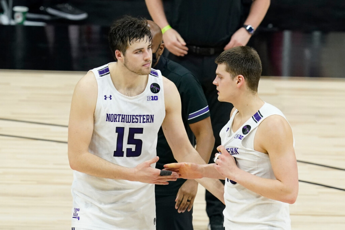 Northwestern's Ryan Young (15) and Miller Kopp (10) leave the court after the Wildcats' loss to Minnesota in the Big Ten tournament.