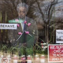 """A cut out of Mayor Lori Lightfoot with a sign next to her that reads """"BEHAVE."""" sits in the front window of the Twisted Hippo in the 2900 block of West Montrose in the Irving Park neighborhood, Tuesday, April 7, 2020."""