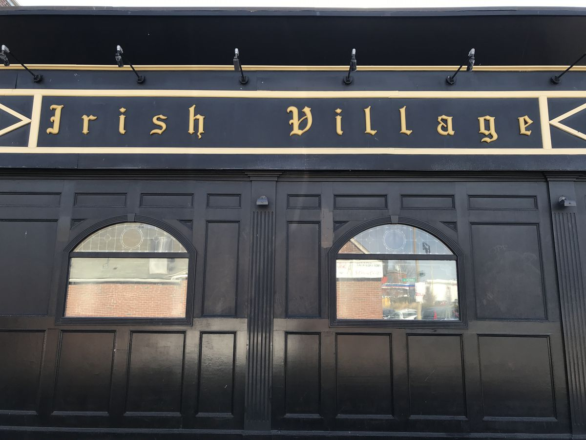Dark wooden exterior of a bar with signage that reads Irish Village in gold, in an old-fashioned font