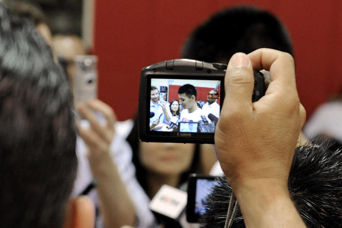 A journalist holds up a camera to photograph Houston Rockets' Jeremy Lin as Lin speaks with the media after NBA basketball practice, Tuesday, Sept. 18, 2012, in Houston.