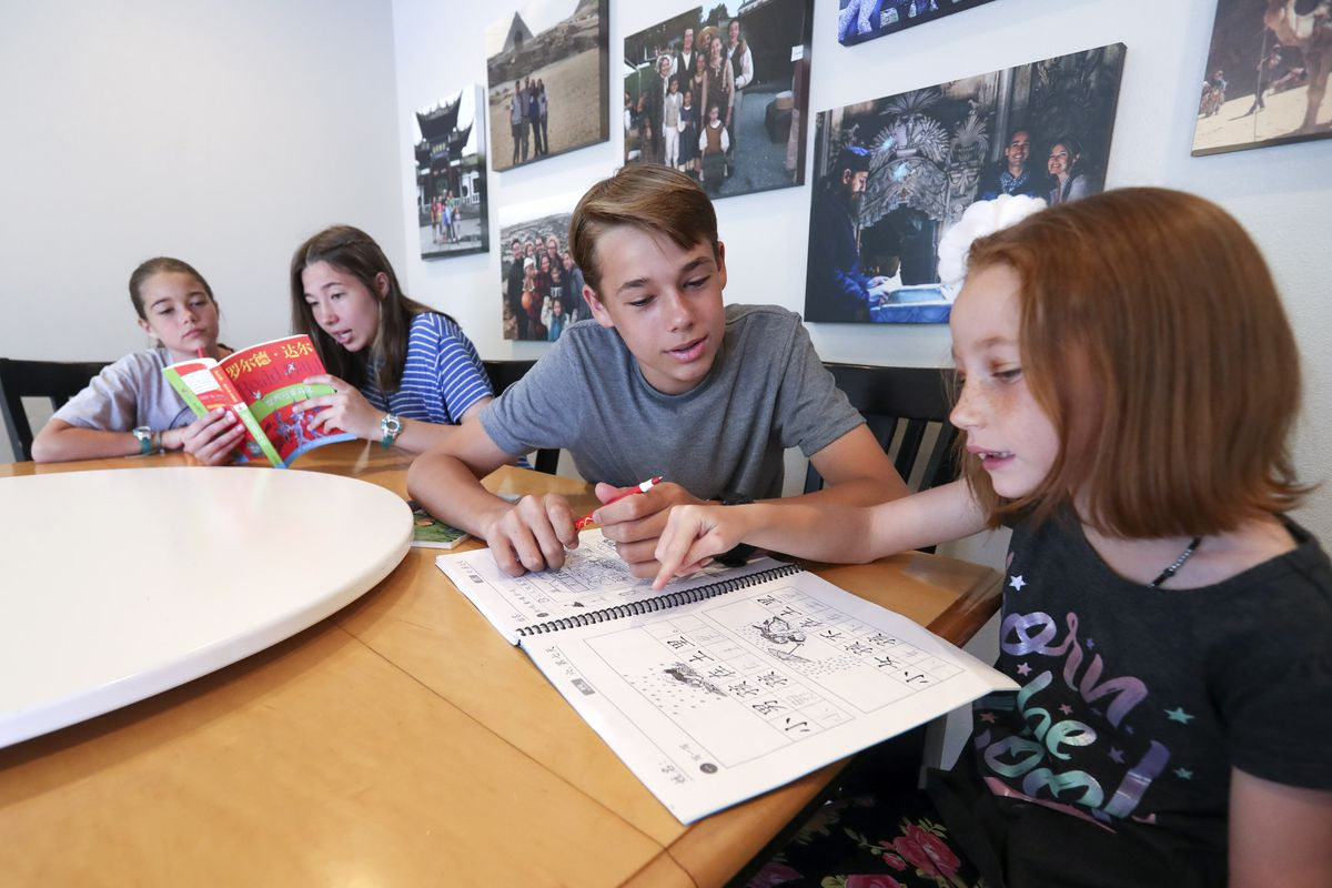 Katrina Hilton, left, listens as her sister, Maria, reads from a book written in Chinese as their brother, Joseph, helps sister, Rebekah, with her Chinese in their home in Orem on Thursday, June 25, 2020. The siblings all attend dual language immersion schools.