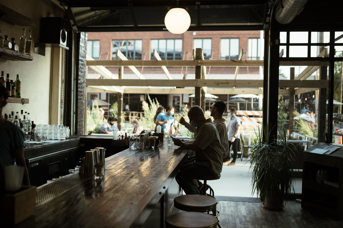 Two people sit at a wooden bar in front of a large open garage door that faces the sidewalk.
