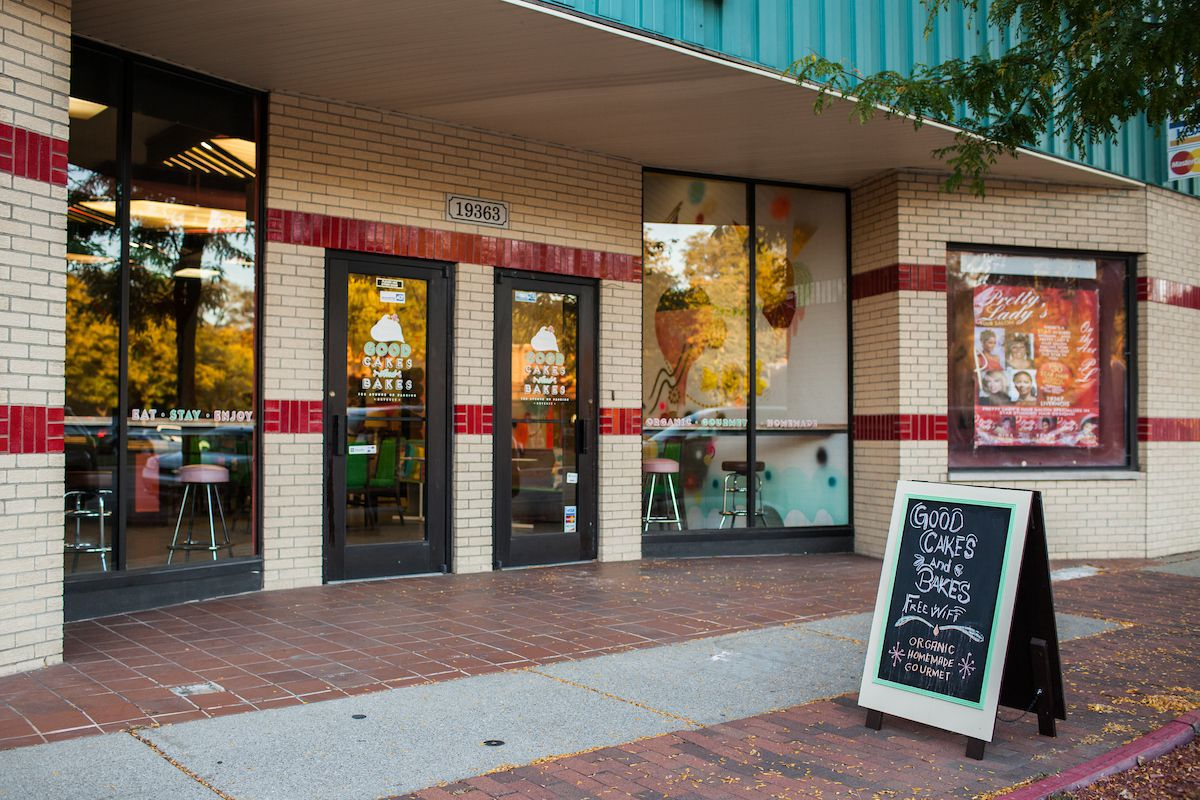 """The storefront at Good Cakes and Bakes has a sandwich board on the sidewalk that reads """"Free WiFi, Organic, Homemade, Gourmet"""""""