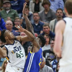 Golden State Warriors center Jordan Bell (2) is charged with a foul as Utah Jazz guard Donovan Mitchell (45) goes to the hoop during the game at Vivint Arena in Salt Lake City on Tuesday, April 10, 2018.
