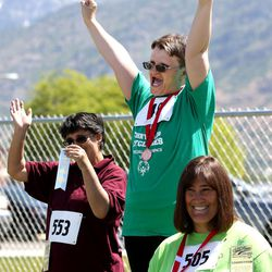 Heidi Hall, of the Chrysalis Cyclones, raises her arms after receiving her first-place medal at the Special Olympics Utah's 48th annual Summer Games at Provo High School on Friday, June 2, 2017. Nearly 1,300 athletes will compete during the two-day event with support from nearly 500 coaches and hundreds of volunteers.