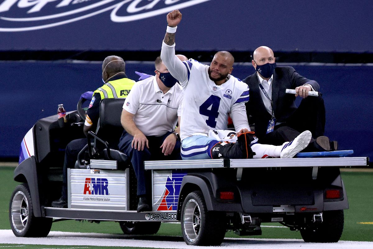 Dak Prescott of the Dallas Cowboys is carted off the field after sustaining a leg injury against the New York Giants during the third quarter at AT&T Stadium on October 11, 2020 in Arlington, Texas.