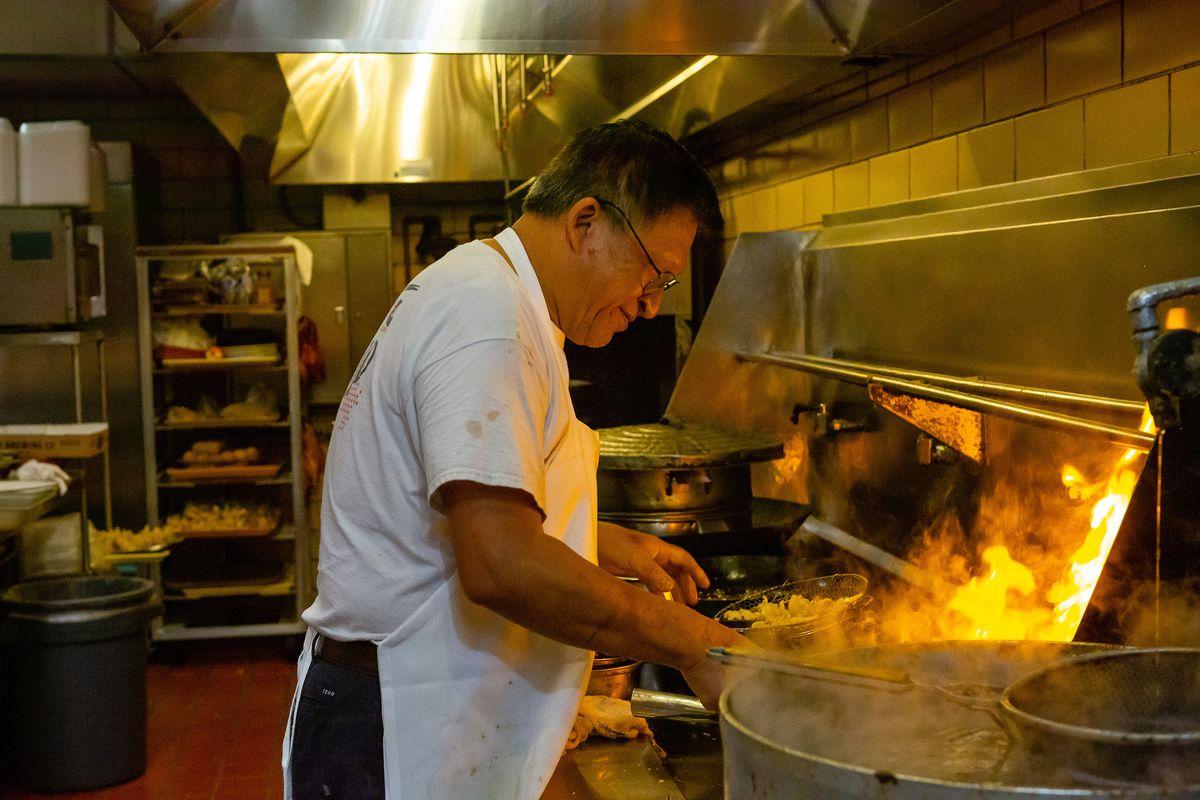 Man wearing apron at a kitchen stove.