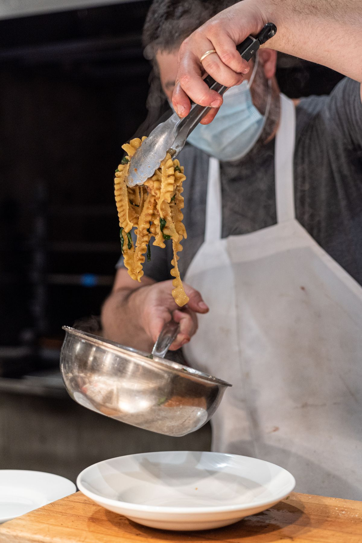 A worker uses tongs from a pan to plate pasta.