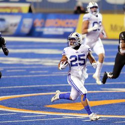 BYU running back Tyler Allgeier (25) looks back to see if he is in the clear as he runs for an 86-yard touchdown as BYU and Boise State play a college football game at Albertsons Stadium in Boise on Friday, Nov. 6, 2020.