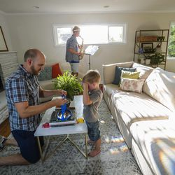 Jon Larsen plays with son George as his oldest son, CS, practices his saxophone at their home in Millcreek on Wednesday, Sept. 16, 2020.