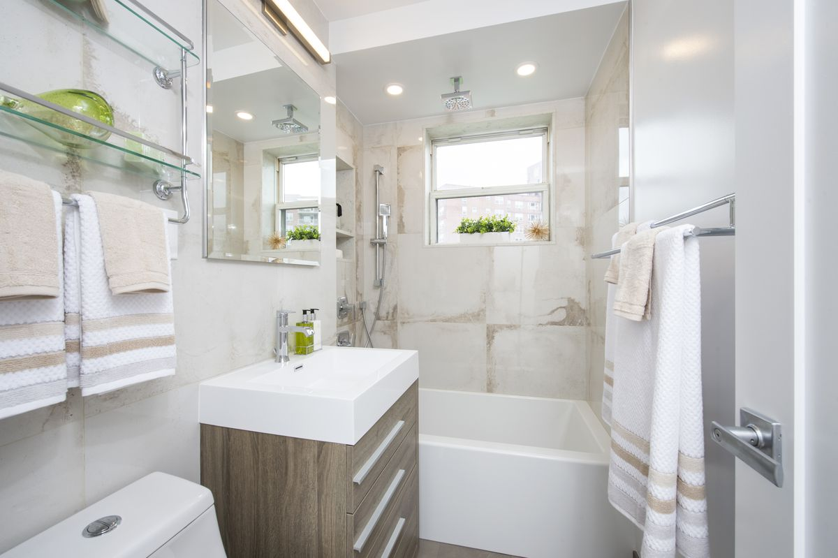 A bathroom with a small window and beige tiles.