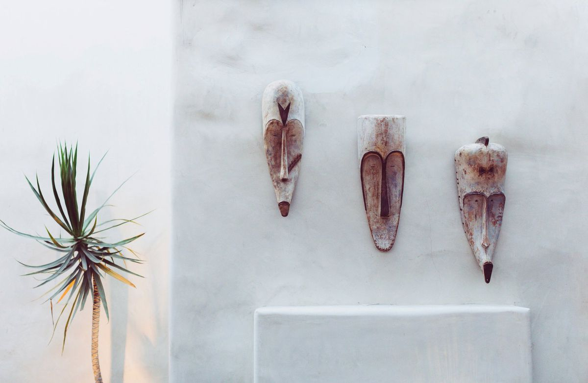 Hanging carved wooden masks sit next to a scrub plant against a whitewashed wall.