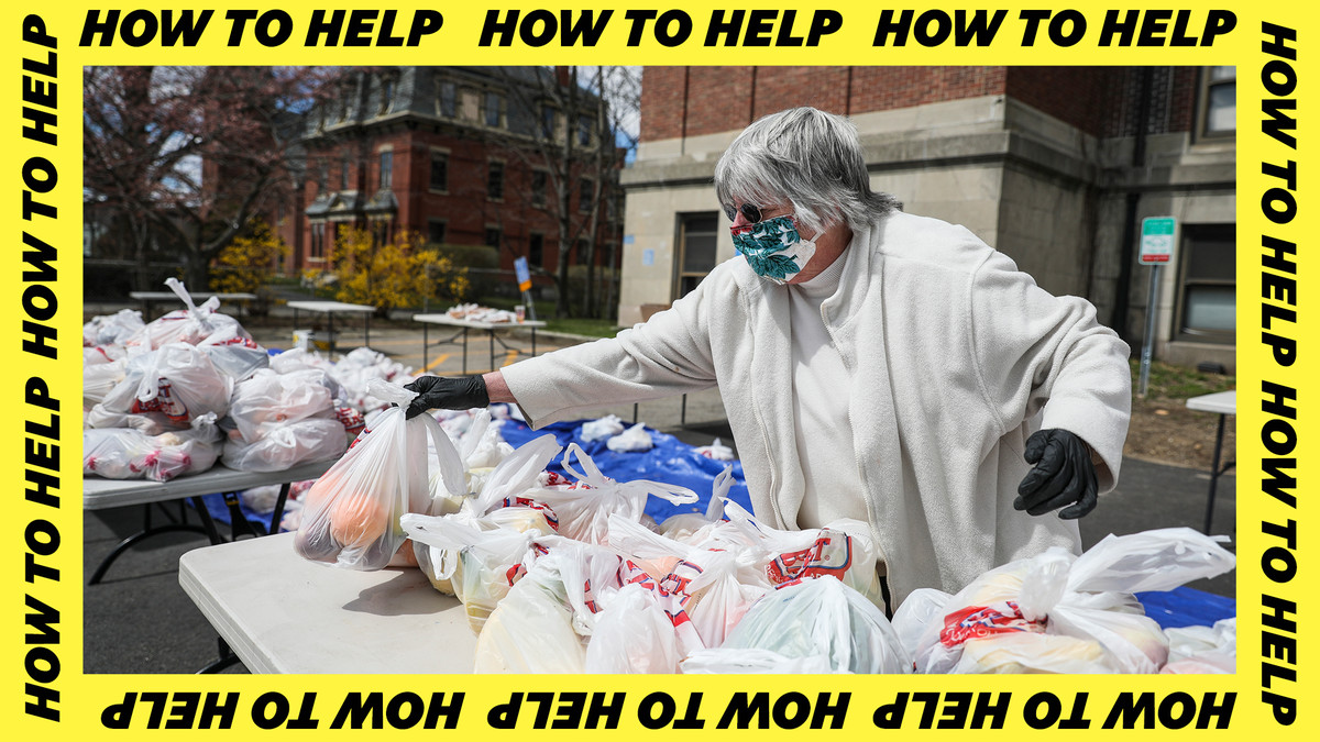 A woman in a mask and gloves sets out grocery bags of food on a plastic table.
