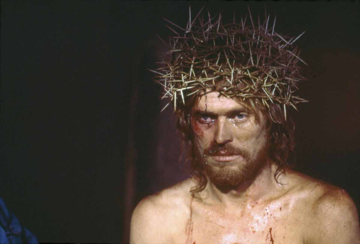 Willem Dafoe dressed as Jesus with a crown of thorns on his head.