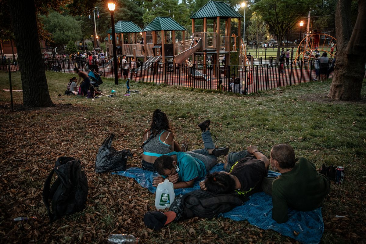 Four people lay on a sheet in the park while a playground is visible in the background.