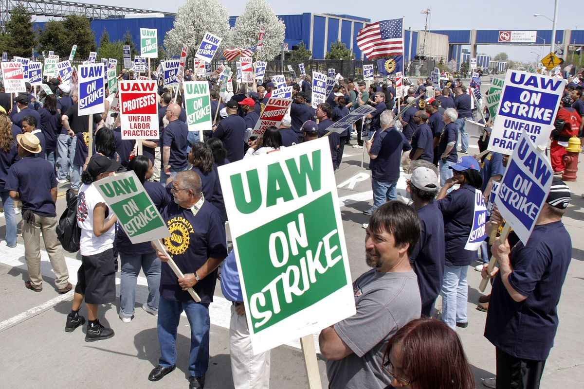 """Auto workers carry US flags and signs reading """"UAW On Strike."""""""