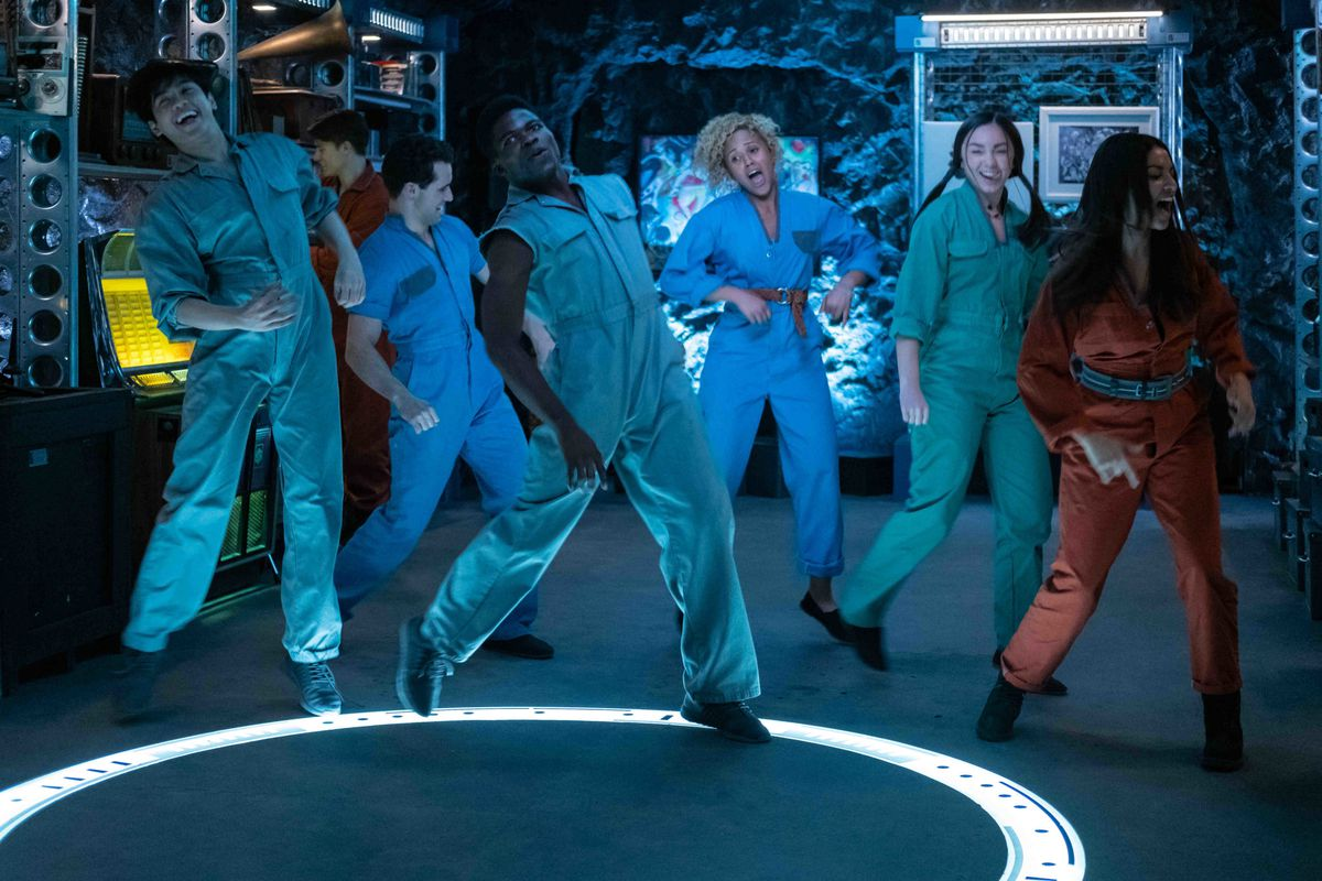 A group of young people in brightly colored jumpsuits dance in unison inside a dark blue cave.