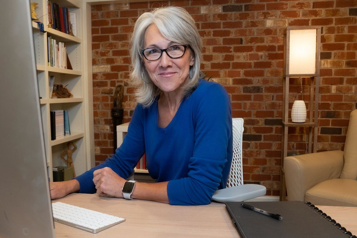 A portrait of Denver Public Schools school board candidate Jane Shirley, who wears a royal blue top and sits at a desk next to bookshelves.