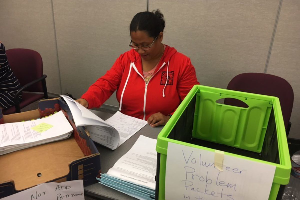 Joi Lin, a Boulder Valley Education Association employee, checks notary pages on petitions for Great Schools, Thriving communities. (Erica Meltzer/Chalkbeat)