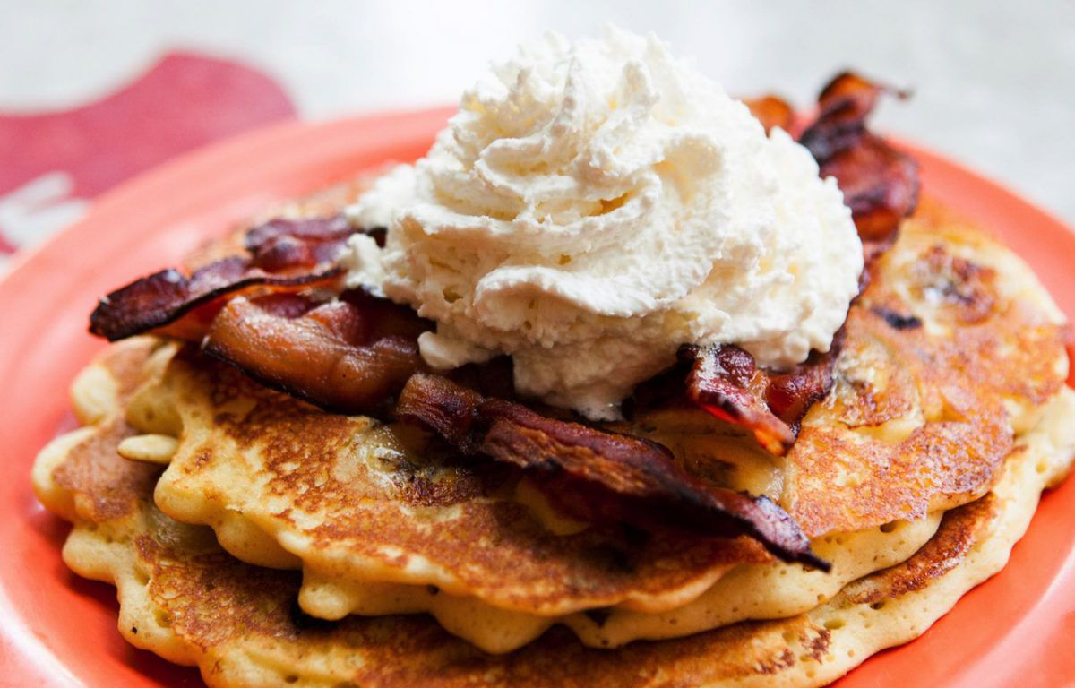 A stack of pancakes sit on a red plate on a red table, topped with bacon and whipped cream