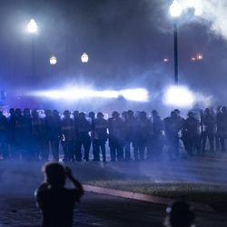 A line of police march down Sheridan Road through a cloud of smoke and tear gas during a protest over the shooting of Jacob Blake, Tuesday, Aug. 25, 2020, in Kenosha, Wis.