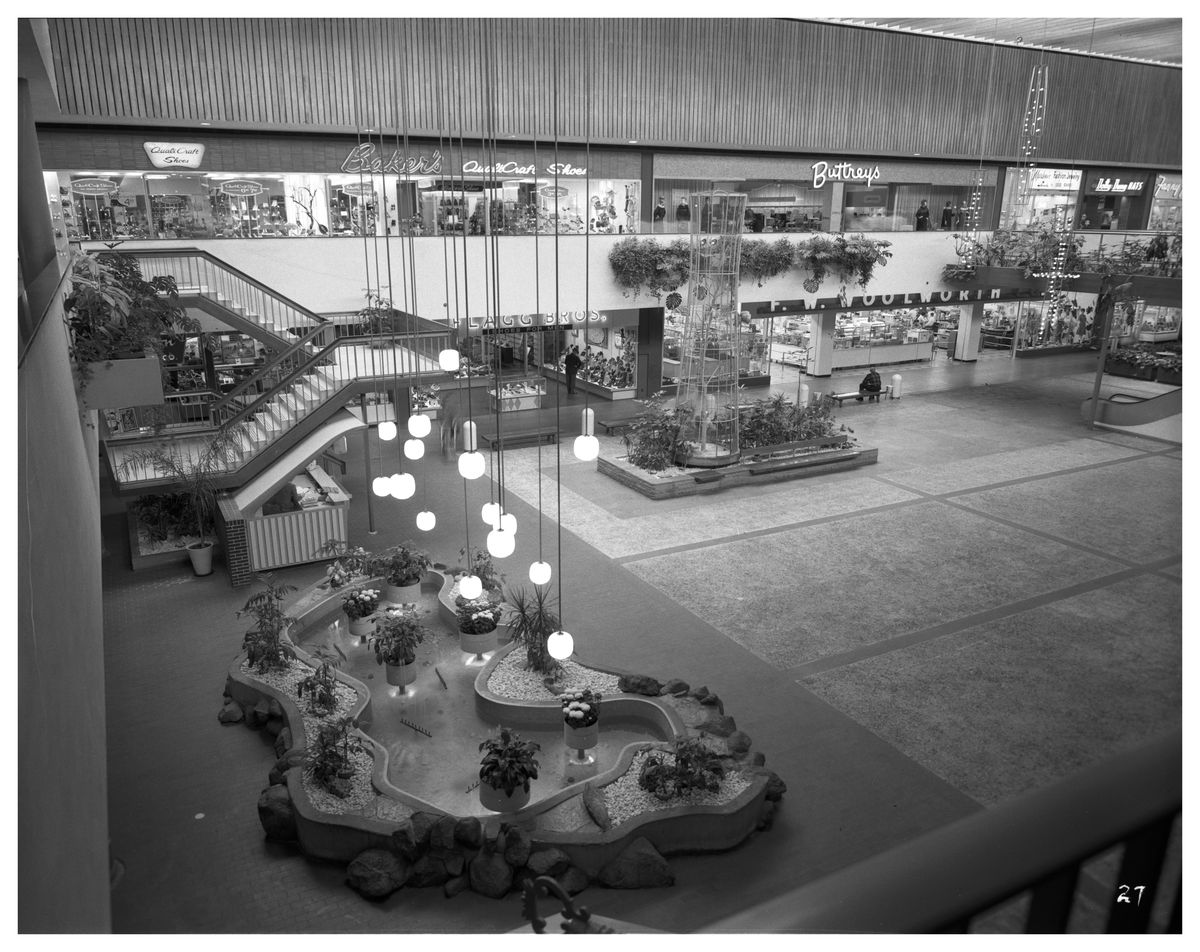 The interior of a shopping mall. There are light fixtures hanging about a fountain in the foreground. Shops surround a large walking area.