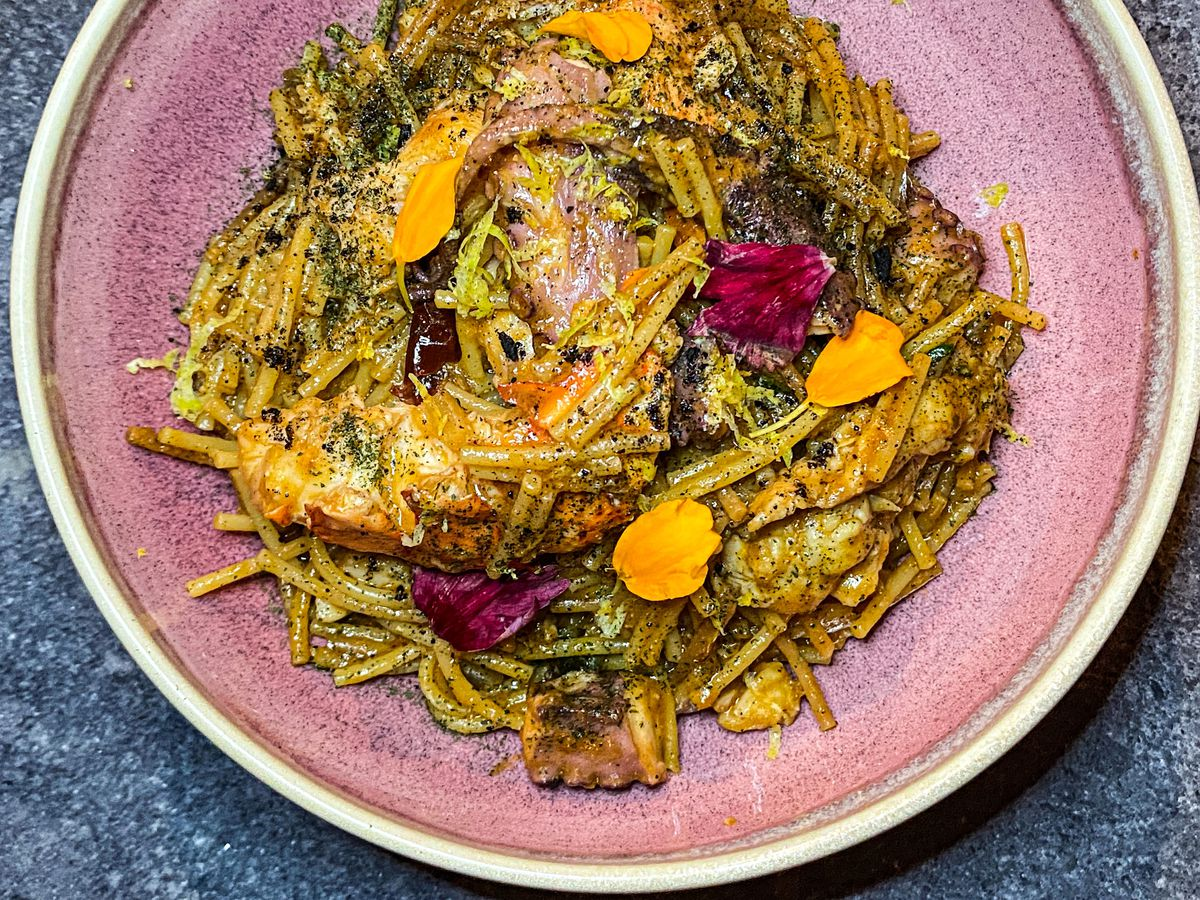 A plate of fideo de mariscos, or seafood pasta, garnished with edible flower petals