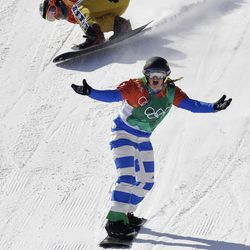 Michela Moioli, of Italy, celebrates winning gold as bronze medal winner Eva Samkova, of the Czech Republic, crosses the finish line after the women's snowboard finals at Phoenix Snow Park at the 2018 Winter Olympics in Pyeongchang, South Korea, Friday, Feb. 16, 2018.